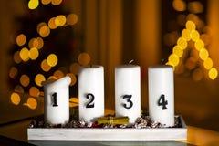 Adventstearinljus i rad med garnering på en ställning med julträdet och en triangelstearinljus på en bakgrund arkivbild