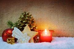 Adventstearinljus med guld- kottar för granträd och julkakor Arkivfoton