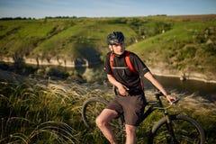 Adventur горного велосипеда Велосипедист имеет остатки на береге реки Стоковые Изображения