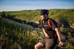 Adventur горного велосипеда Велосипедист имеет остатки на береге реки Стоковая Фотография