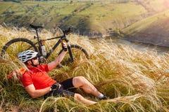 Adventur горного велосипеда Велосипедист имеет остатки на береге реки Стоковая Фотография RF