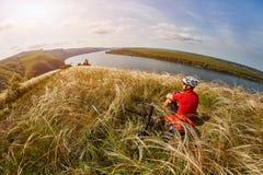 Adventur горного велосипеда Велосипедист имеет остатки на береге реки Стоковое фото RF