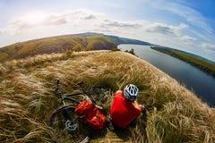 Adventur de la bici de montaña El ciclista tiene un resto en la orilla Imagen de archivo