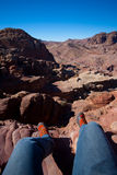 Adventure. Sitting on a cliff, steep drop Royalty Free Stock Photography