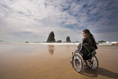 Adventure. Beautiful young woman in a wheel chair visiting Canon Beach in Oregon, USA Royalty Free Stock Photos