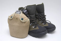 Adventure. Canteen and hiking boots isolated Royalty Free Stock Photography