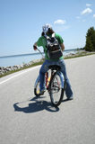 Adventure. A girl on a bike pauses as she rounds a curve in a road that follows the shore. The girl is wearing a bandana and a green t-shirt stock images