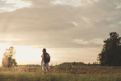 Adventure. Alone into the meadow at sunset Royalty Free Stock Photos