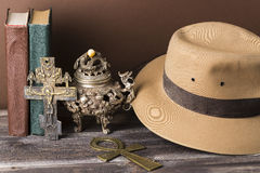 Adventure and archeological concept for lost artifacts with hat, vintage books, iron vase, key of life, vintage cross on wood tabl Stock Photography