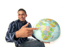 Adventure awaits. Chap points out where his adventure awaits on the globe Royalty Free Stock Images