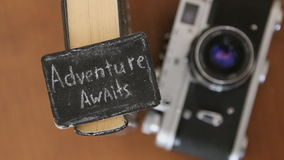 Adventure awaits  idea. Adventure awaits - inscription, book and old camera stock footage