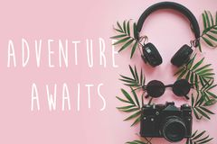 The Adventure Awaits text on stylish photo camera with green pal. M leaves, sunglasses and headphones on trendy pink paper. modern summer vacation image, stylish royalty free stock photography