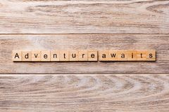 Adventure awaits word written on wood block. Adventure awaits text on wooden table for your desing, concept.  stock image