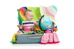 Adventure. Baby preparing for the journey. Child sits in suitcase and looks at globe. Adventure concepts. Baby preparing for the journey. Child sits in suitcase Stock Photos