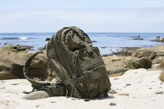 Adventure backpack on sand with ocean in background Royalty Free Stock Photography