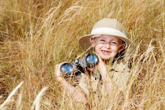 Adventure boy. Young boy plays safari explorer with binoculars and bush hat in a field. happy adventure seeking kid playing outdoors stock photos