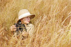 Adventure boy. Young boy plays safari explorer with binoculars and bush hat in a field. happy adventure seeking kid playing outdoors stock images