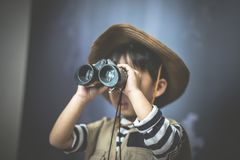 A adventure boy is preparing a camera and a binocular. A adventure boy is preparing a camera and a binocular for travel the jungle Royalty Free Stock Photo