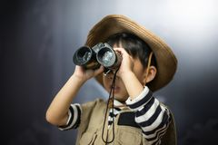A adventure boy is preparing a camera and a binocular. A adventure boy is preparing a camera and a binocular for travel the jungle Stock Photos