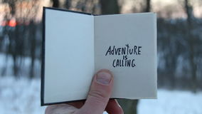 Adventure is calling, travel idea. Book and text. Adventure is calling. Hand holding a book with the inscription stock footage