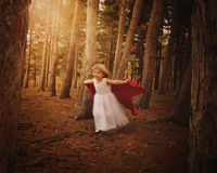 Adventure Child Running in Woods with Fall Leaves. A little girl wearing a white dress and red cape is flying in the wind in the woods with fall leaves for a stock image