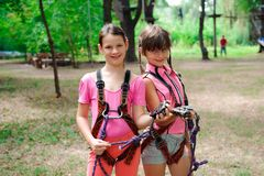 Adventure climbing high wire park - hiking in the rope park two sisters teenagers in safety equipment. Adventure climbing high wire park - hiking in the rope stock images