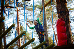 Adventure climbing high wire park - kid on course in  helmet and safety equipment Stock Image