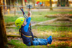 Adventure climbing high wire park - kid on course in  helmet and safety equipment Royalty Free Stock Photography