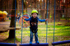 Adventure climbing high wire park - kid on course in  helmet and Royalty Free Stock Image