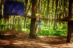 Adventure climbing high wire park - little child on course in mountain helmet and safety equipment Stock Photo