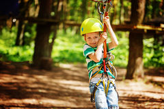 Adventure climbing high wire park - little child on course in mountain helmet and safety equipment.  Stock Images