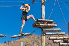 Adventure climbing rope park - a young woman walks along logs and ropes at a height against the background of mountains and blue s Stock Image