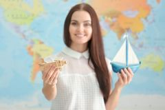 Adventure concept. Beautiful woman holding traveling symbols. On map background Stock Photo