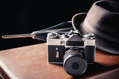 Adventure concept. Old film camera with vintage hat and umbrella on old brown suitcase. Vintage toned Royalty Free Stock Photo