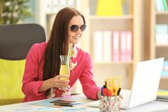 Adventure concept. Young woman dreaming about tropical vacation sitting. At workplace Royalty Free Stock Images