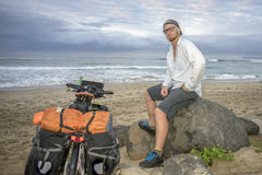 Adventure Cyclist on Beach by Bicycle. An adventure cyclists sits on a rock by the beach and ocean with his packed bicycle standing next to him royalty free stock photography