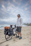 Adventure Cyclist on Beach with Bicycle. A long distance adventrure cyclist stand on the beach with his packed bicycle beside him as he looks out over the ocean royalty free stock photos