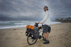 Adventure Cyclist with Bicycle on Beach. A long distance adventure cyclist stands with his bicycle in hands on the beach while looking at the ocean royalty free stock photo