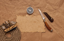 Adventure decoration with compass on old paper. Old paper, rope coil, compass, decorative knife and model classic boat Stock Image