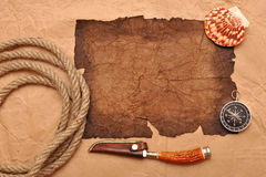 Adventure decoration with compass on old paper. Old paper, rope, compass, decorative knife on old paper Stock Images