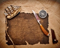 Adventure decoration with compass on old paper. Old paper, rope, compass, decorative knife and model classic boat on very old paper Stock Image