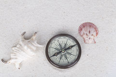 Adventure decoration with compass, shell and conch on the white sand. Royalty Free Stock Photos