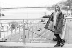 Adventure, discovery, journey. Child in red coat stand on bridge. Kid enjoy autumn day on blurred urban landscape. Girl with blond long hair smile outdoor stock image