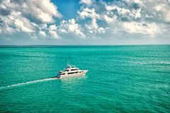 Adventure, discovery, journey. Yacht sail in turquoise sea on cloudy sky. Water transport, vessel, boat, transportation. Vacation wanderlust travelling Luxury stock photography