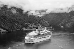 Adventure, discovery, journey. Cruise ship in norwegian fjord. Passenger liner docked in port. Travel destination. Geiranger, Norway - January 25, 2010 royalty free stock images