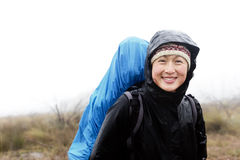 Adventure expedition rain trek. Portrait of asian hiker with waterproof gear and backpack in the rain while trekking on an adventure expedition in the mountains Royalty Free Stock Image
