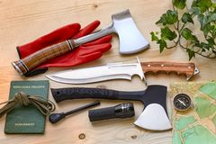 Adventure and explore with compass, passport, axes, knife, fire starter and tools for outdoor life Stock Photography