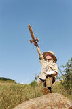Adventure explorer child. Adventure explorer treasure map boy with wooden sword plays outdoors in a field having fun royalty free stock photo