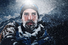 Adventure explorer mountain man. Adventure mountain man in snow blizzard looking on with determination and courage Stock Photography