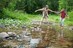 Adventure in forest. Young couple of tourists crossing river during forest adventure Stock Images